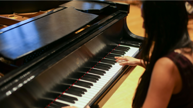 Student playing the piano in a Music program