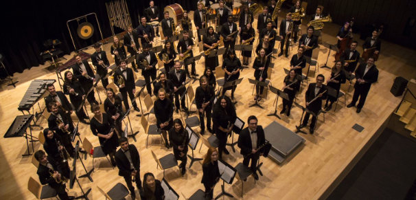 A large concert band arranged in a semi-circle on stage